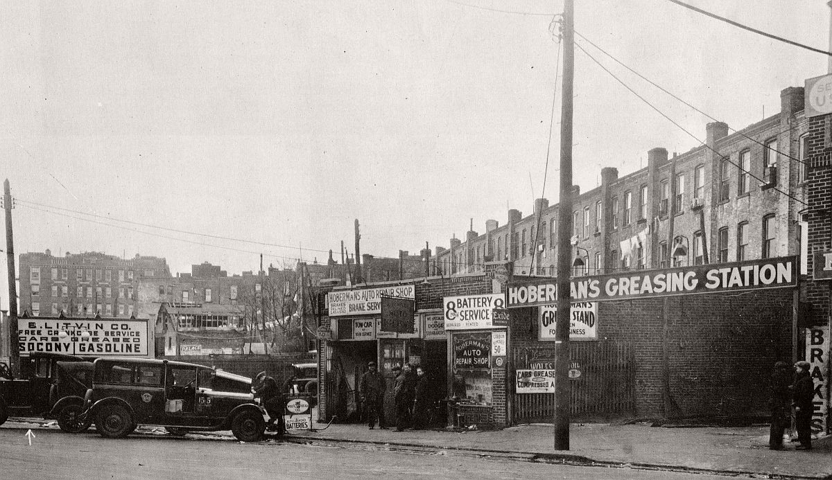 Socony gas station specializing in Dodge and Studebaker. Wolf's Head Oil, cars greased, carbon removed for 50 cents, batteries repaired. Everything you need for your 1920s car! East New York Ave by Howard Ave. Brooklyn, 1928