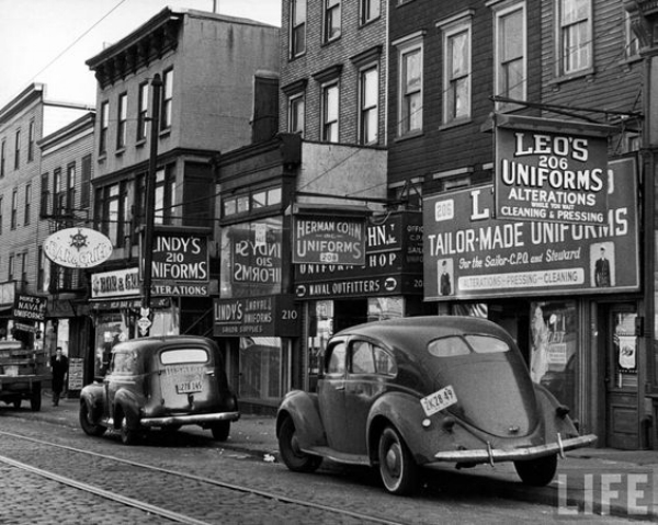 Cars parked in front of four Navy uniform stores on Sand Street, Brooklyn, 1946