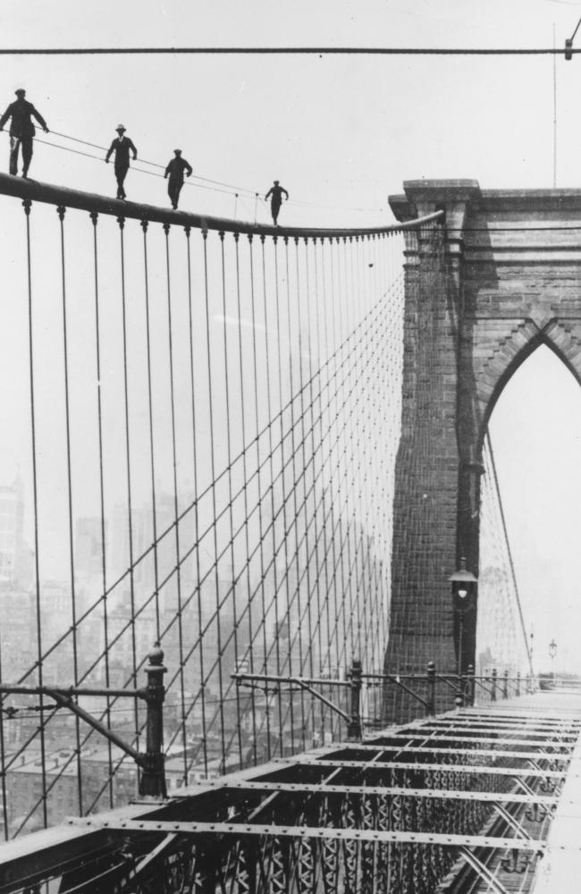 Four men climb Brooklyn Bridge in New York City, 1914