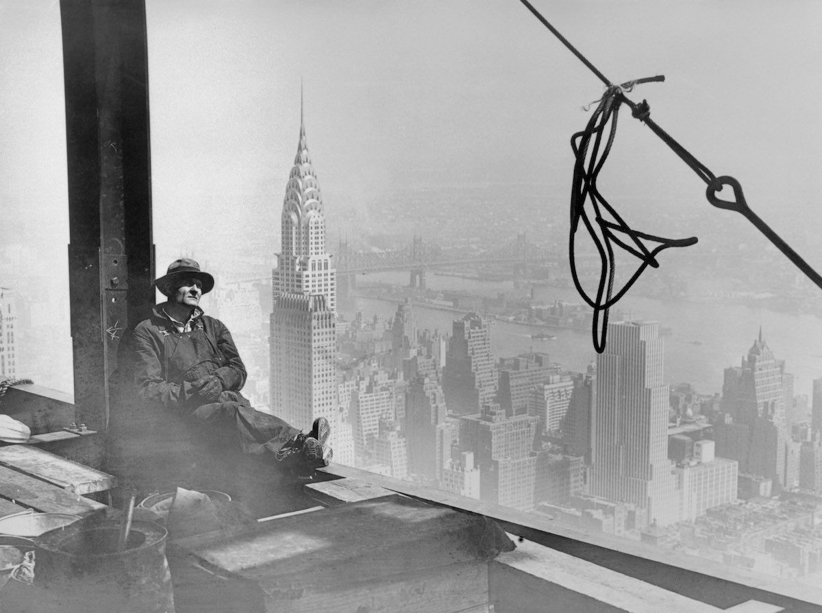 This worker seems alone in his thoughts, at a dizzying height with Chrysler Building in background. New York, 1930