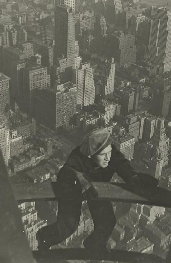 A worker hanging on to two beams during construction of the Empire State Building, 1931