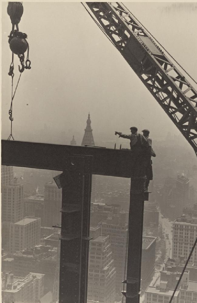 Two construction workers at the corner of two steel beams point to their left during construction of the Empire State Building, 1931