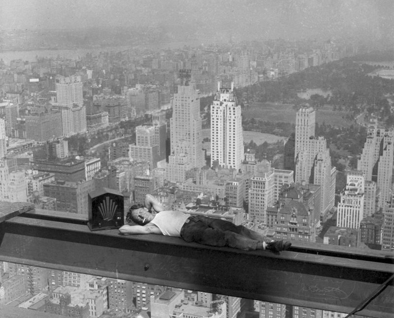 A daredevil construction worker relaxing on a steel beam having a break from the building of the Rockefeller Center, New York, 1932
