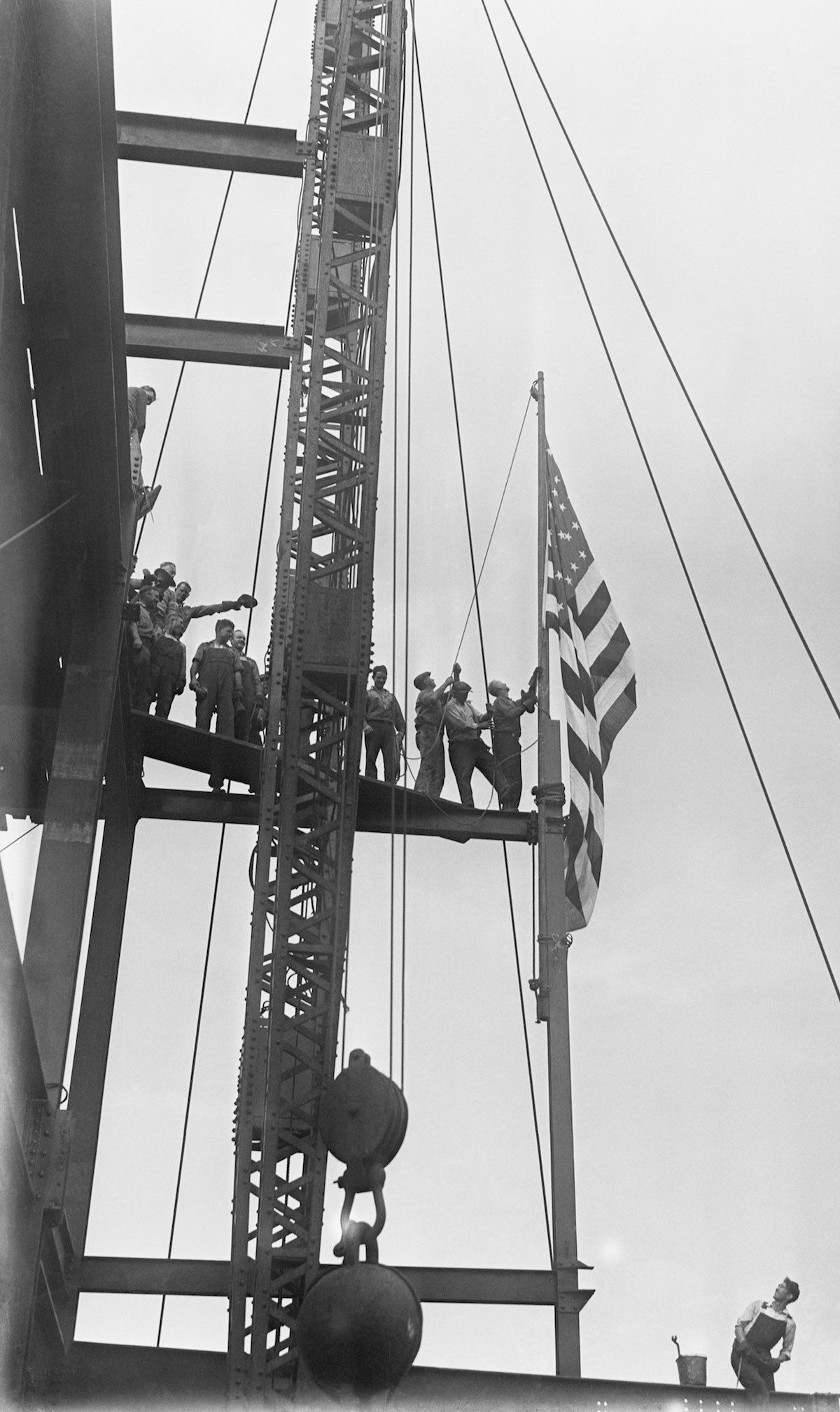 Workmen at the new Empire State Building raising the American flag on the 88th story of the great building, 1,048 feet above the street. The flag was the highest point in the city higher then the Crystler Building in September 1930.