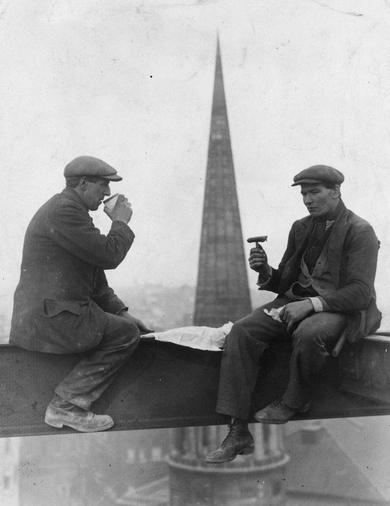 Two construction workmen take a break for lunch in front of the spire of All Souls Church, London, c. 1940