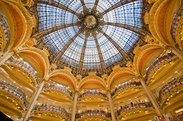 Galeries Lafayette  The Galeries Lafayette, a palatial flagship department store that first opened its door to public in 1912, offers both retail and architectural splendor. Peer up from its bowed balconies at a dramatic cupola in a turn-of-the-century palette.(Courtesy of www.architecturaldigest.com)