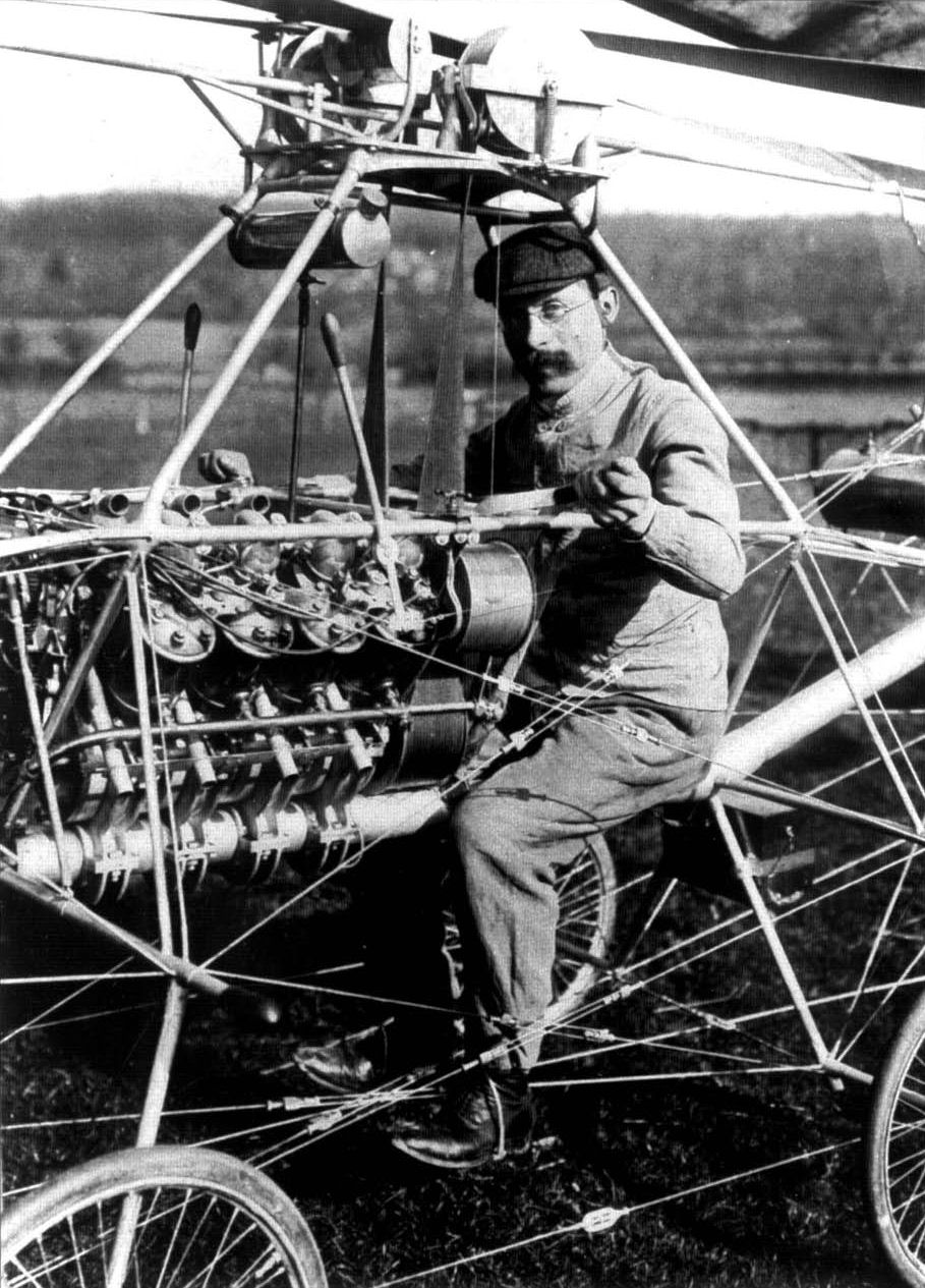 French engineer Paul Cornu in his first helicopter in 1907. Note that he is sitting between the two rotors, which rotated in opposite directions to cancel torque. This helicopter was the first flying machine to have risen from the ground using rotor blades instead of wings.