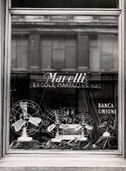 """The shop window of a boutique selling """"Ercole Marelli"""" fans, Milan, 1952"""