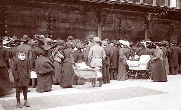 These crowded people are waiting for the unveiling of a Christmas toy display, 1910s