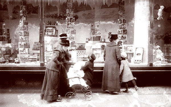 Mothers with their children looking at a colorful display of toys and games, Macy's holoday display,1915.