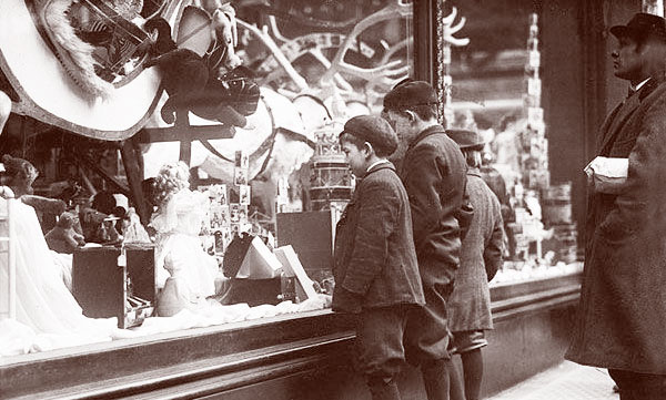 Children window shopping, looking at toys in a Christmas display, early 1920s
