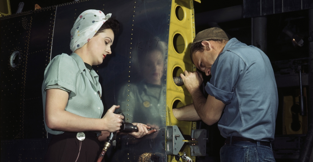 A woman rivets an airplane wing at a munitions factory, 1940s