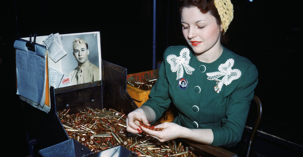 A woman inspects machine gun bullets at Remington Arms Company's Bridgeport, Connecticut, near the desk a photo of her husband who is serving overseas, 1940s