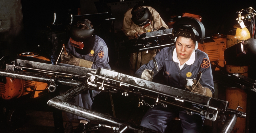 Members of a riveting team at an aircraft factory use rivet guns and bucking bars to work on a basis trainer plane wing center section, 1940s