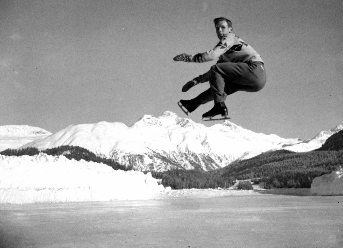 The beautiful panorama around Lake St. Moritz for this Dick Button of Englewood's jump during a practice session in preparation for the Winter Olympics, 1948