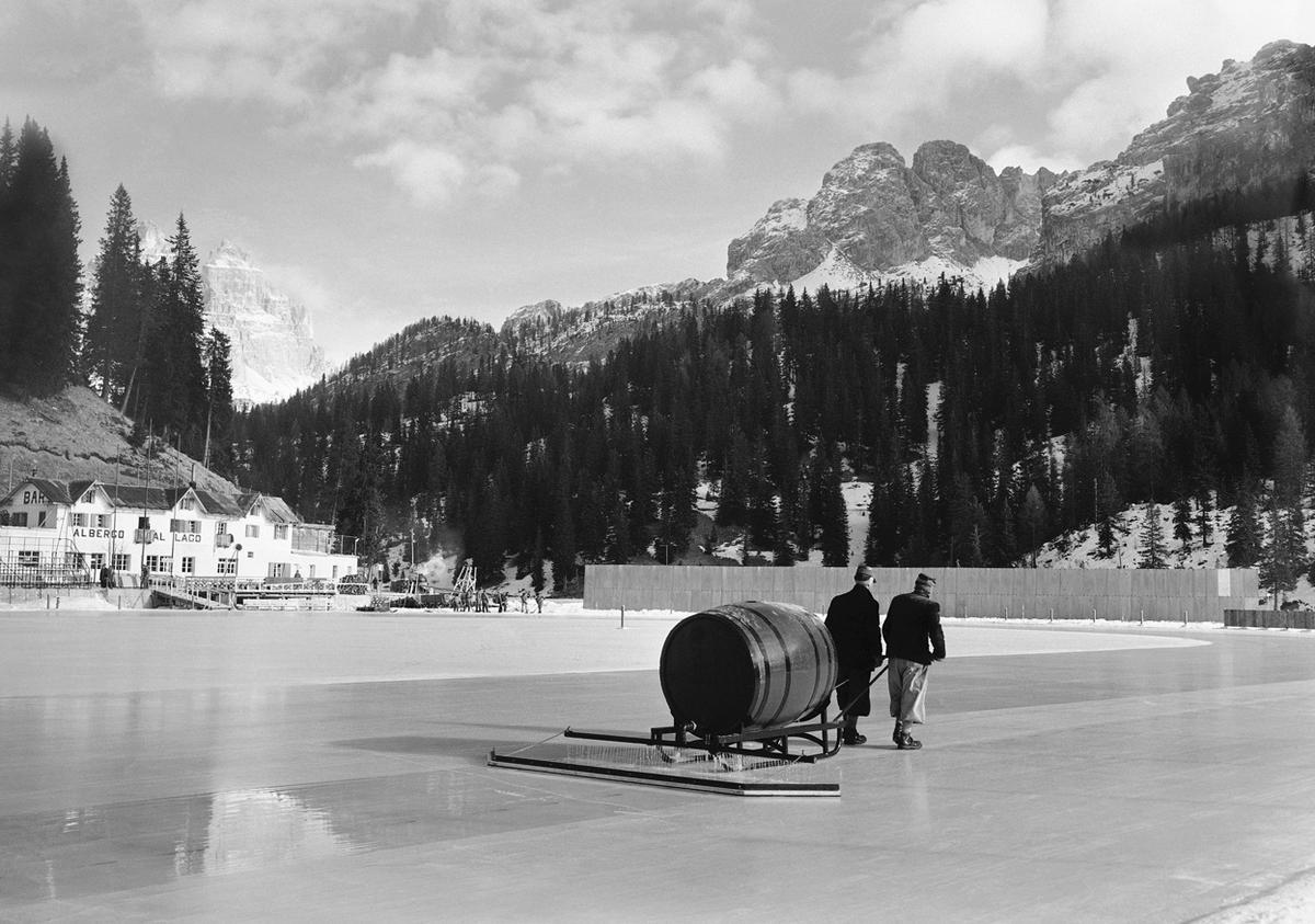 To form a fresh smooth surface, lukewarm water is poured over the ice of the speed skating rink of Lake Misurina, where the 1956 Winter Olympics speed skating events will take place in Cortina d'Ampezzo, Italy