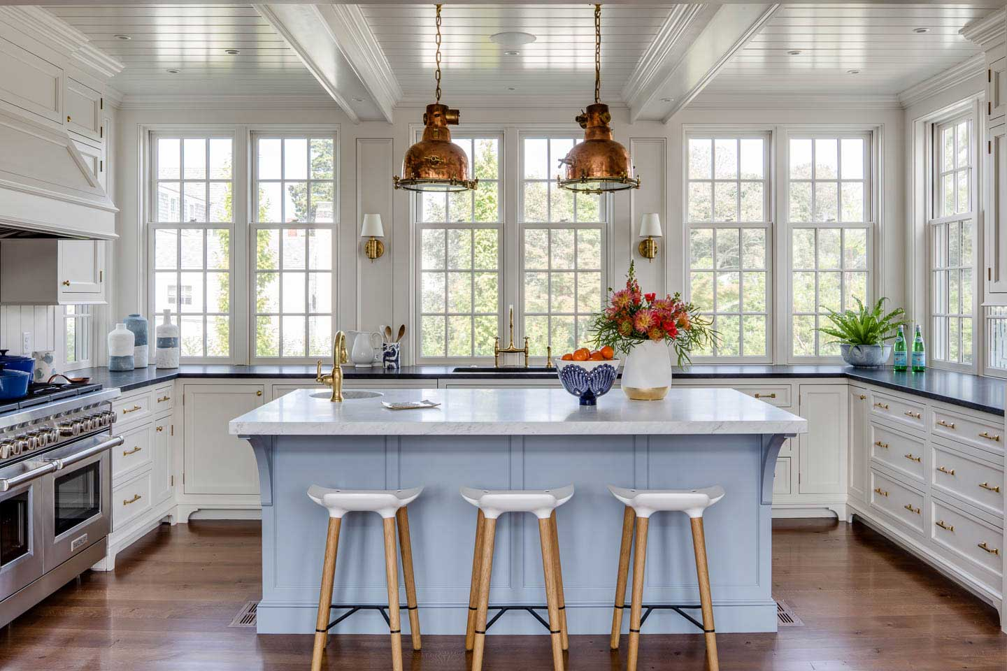 cape cod kitchen, light blue island, white cabinets, island seating, stools, marble counter, island sink, pendant lights, island lighting, copper lights, shiplap ceiling, wall of windows