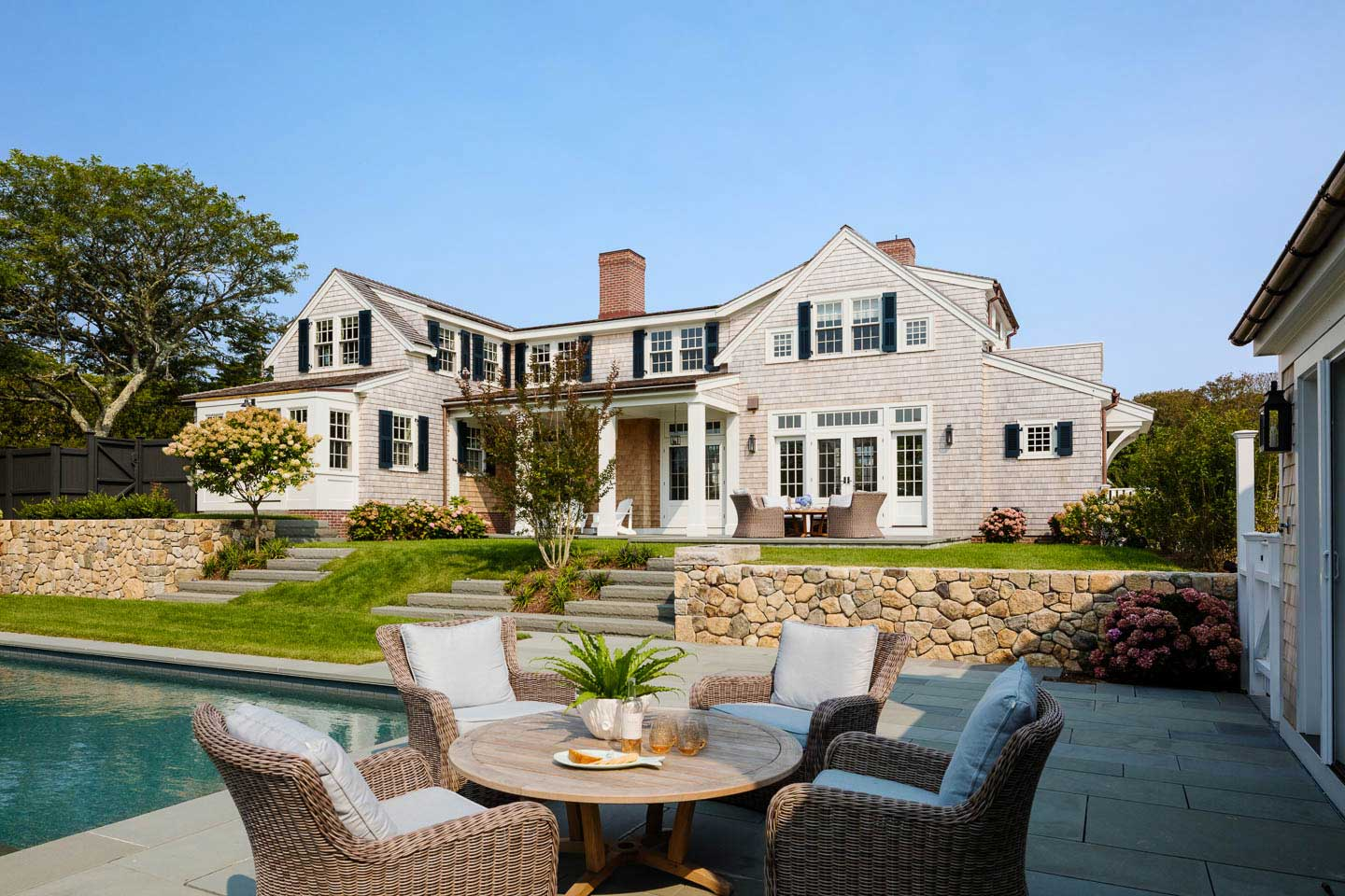 cape cod house, pool, outdoor seating, stone wall, outdoor dining, backyard