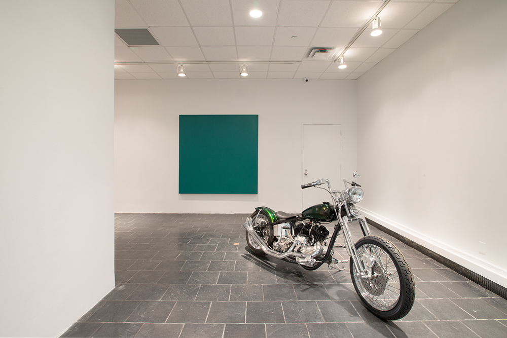 Installation view:  Olivier Mosset , Hunter College Art Galleries, 2016. Photo by Bill Orcutt. Left to right:  U2 , 2015. Acrylic on canvas, 72 x 72 in. Galerie Andrea Caratsch, Zurich / St. Moritz.  Flathead 1954 . 1954 Harley Davidson, 45 cubic in, 750 cubic cm. Courtesy of the artist and Martos Gallery, New York.