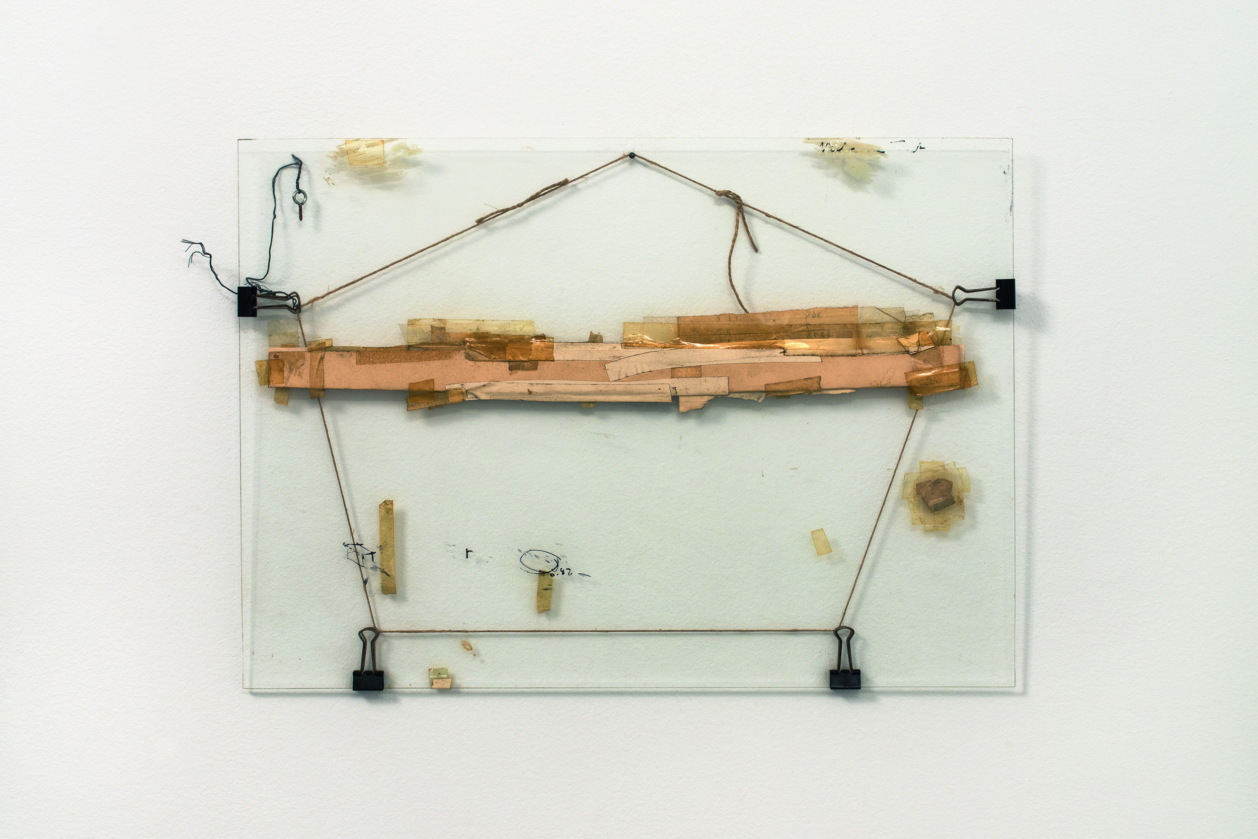 Nahum Tevet, Untitled #3, 1972, restored by the artist, 2016. Cardboard, binder clips, twine, wire, screw eye, masking tape, transparent tape, plastic tape, marker, and wax pencil on glass, 13 3/4 x 19 3/8 x 7/16 in. (34.9 x 49.2 x 1.1 cm). Collection of the artist. Photo by Polite Photographic, courtesy of the Hunter College Art Galleries and the artist.