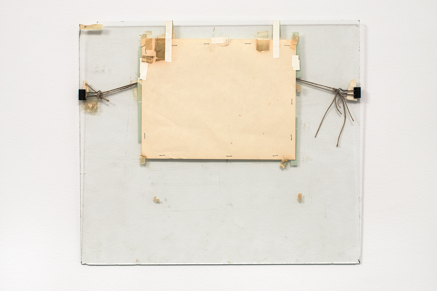 Nahum Tevet, Untitled #5, 1972. Paper, binder clips, twine, staples, plastic tape, masking tape, transparent tape, and wax pencil on glass, 17 3/16 x 19 3/4 x 7/16 in. (43.7 x 50.2 x 1.1 cm). Collection of the artist. Photo by Polite Photographic, courtesy of the Hunter College Art Galleries and the artist.