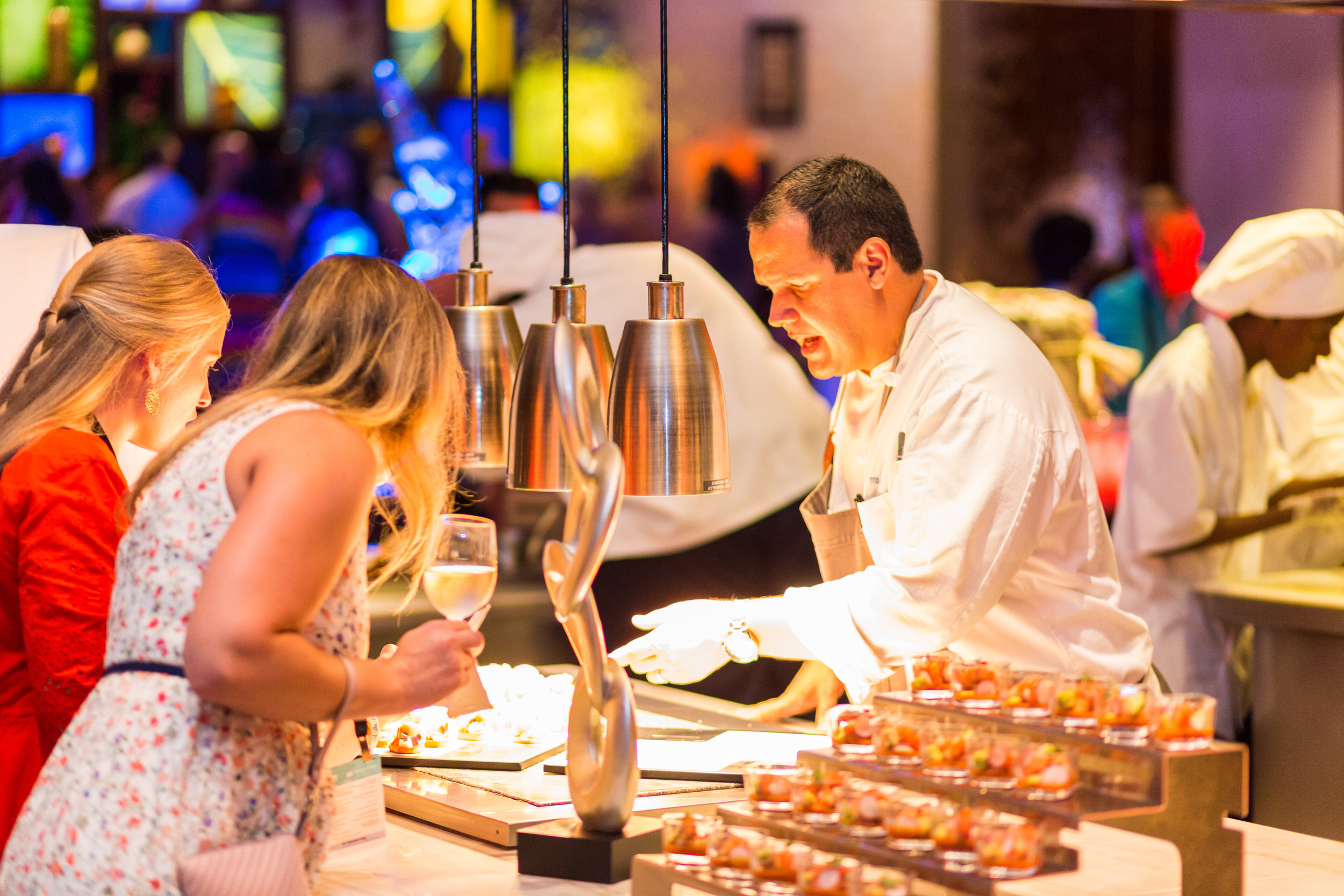 An Atlantis chef explaining his dish to inquisitive attendees.