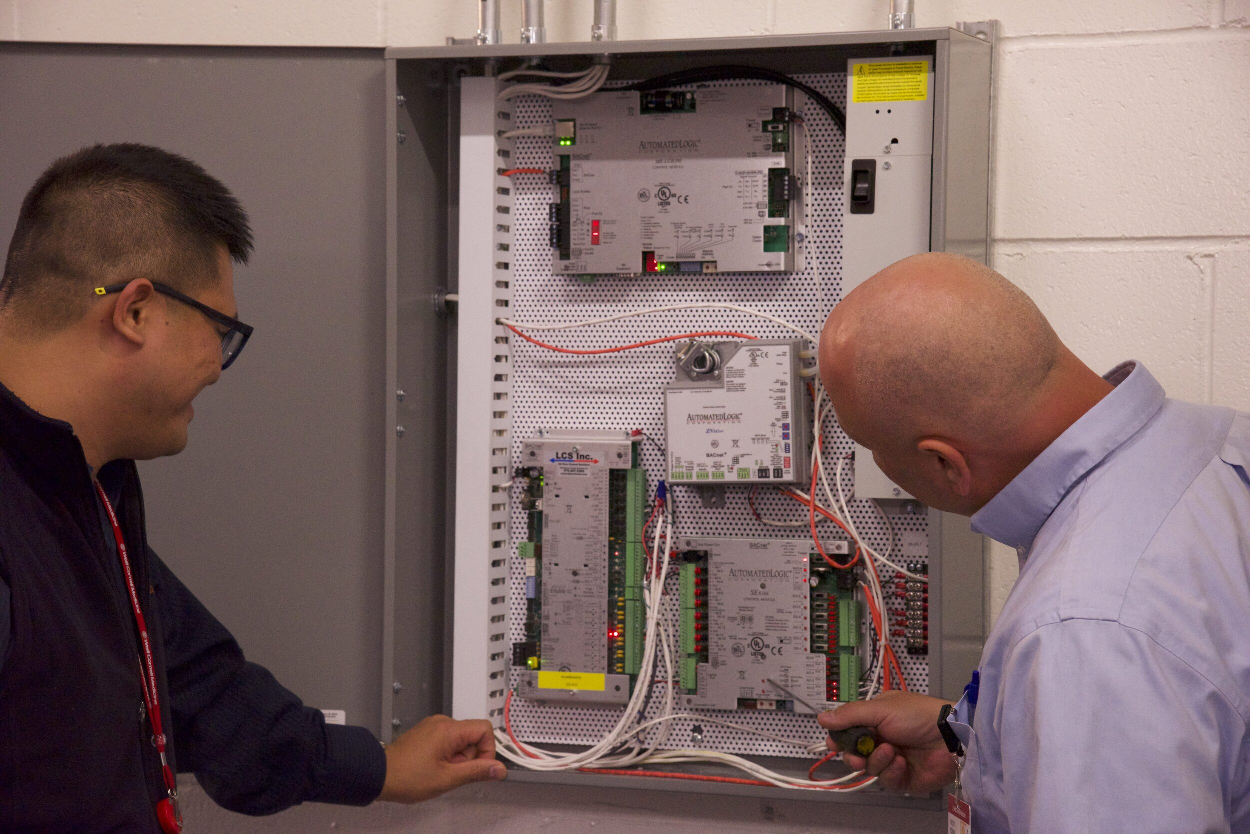 HARRY TEPPER AND VINcent ROMANO LOOKING AT ONE OF THE SYSTEMS IN THE LEARNING LAB.