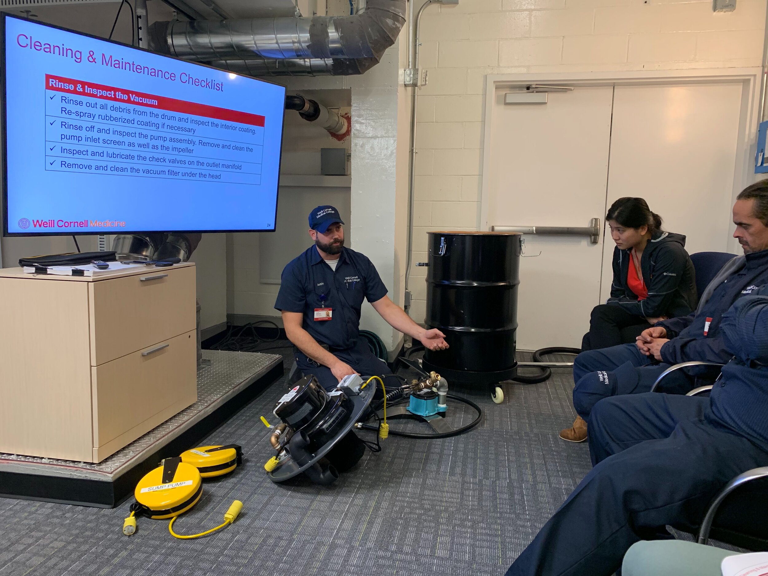 JUSTIN ERRANTE LEADing A TRAINING ON A LARGE VOLUME WET/DRY VACUUM.