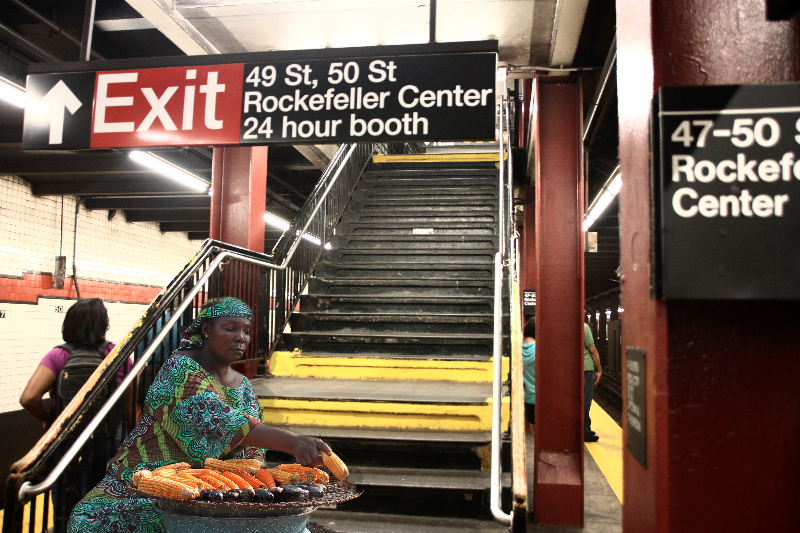 A Woman From Marina, Lagos Roasting Corn And Ube In A Subway Station In New York.