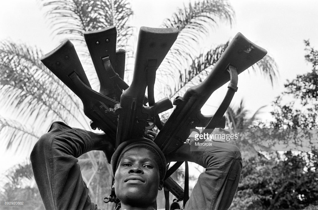 A Biafran Soldier Holding Guns.