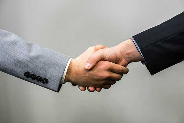 We offer financial advice in Prescott, AZ with the commitment of alway acting as a fiduciary. Graphic is of a handshake.
