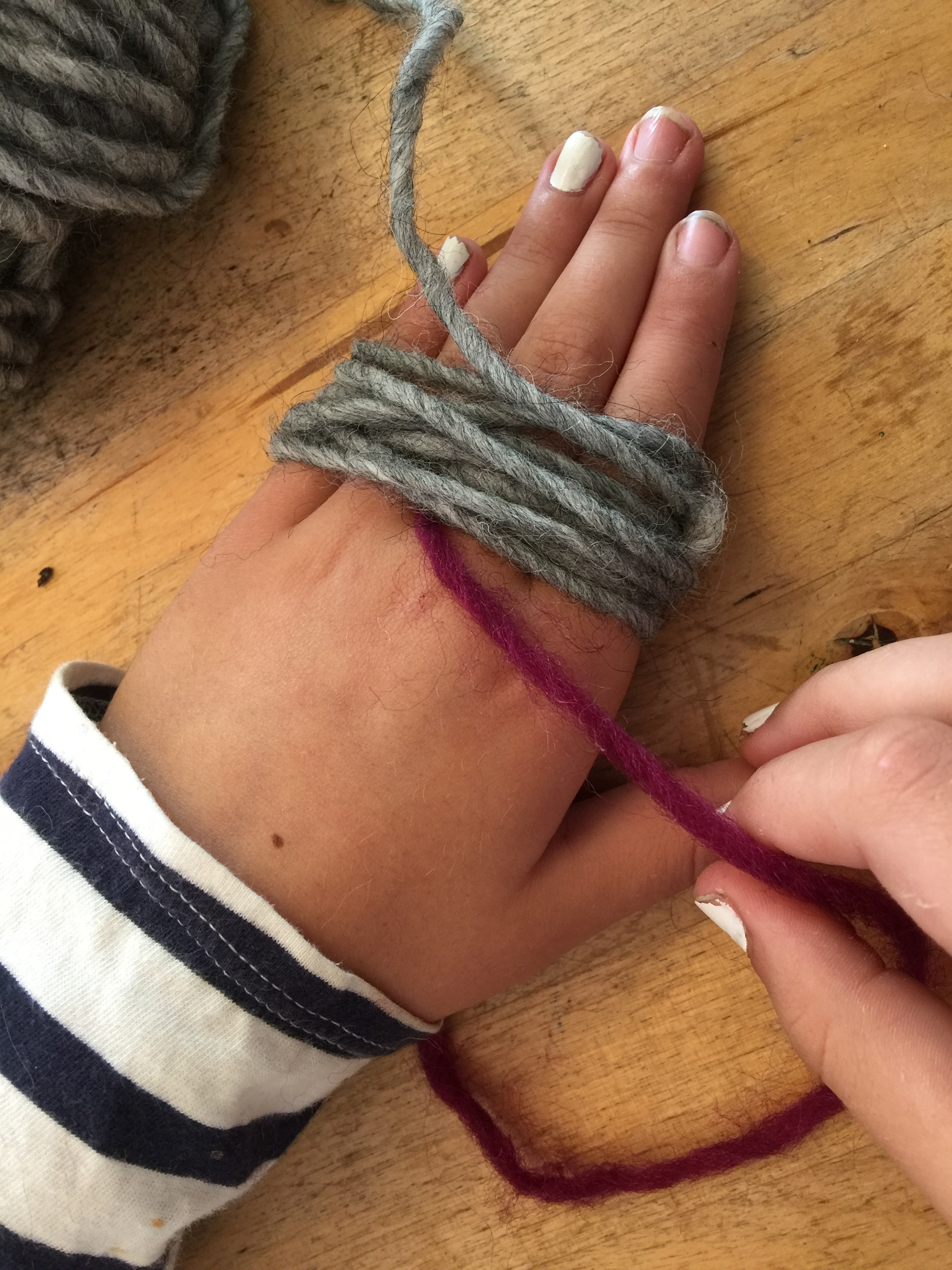 Wrap your four fingers in wool, not too tightly, but lots and lots of times... we counted to 50 rotations.The trick to a fat fluffy pom-pom is inthe wrapping - the more you wrap, the plumper they become.