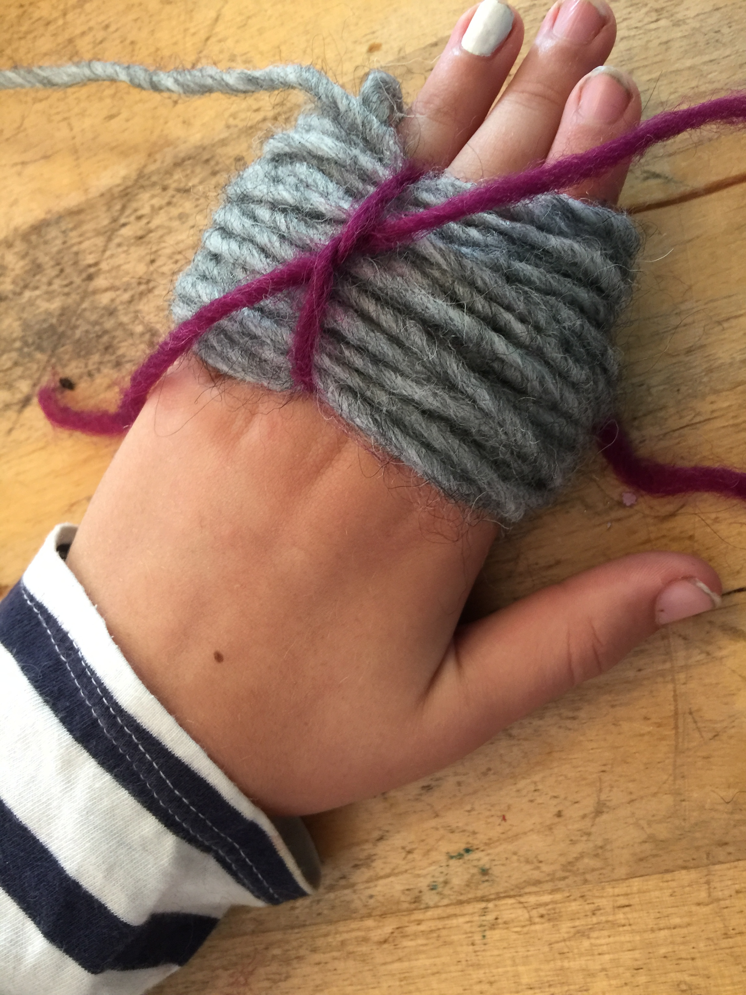 Once those fingers are wrapped in a fat layer of woolly loops, bring the strands forward and use them to tie the loops together tightly, into a figure 8 shape.