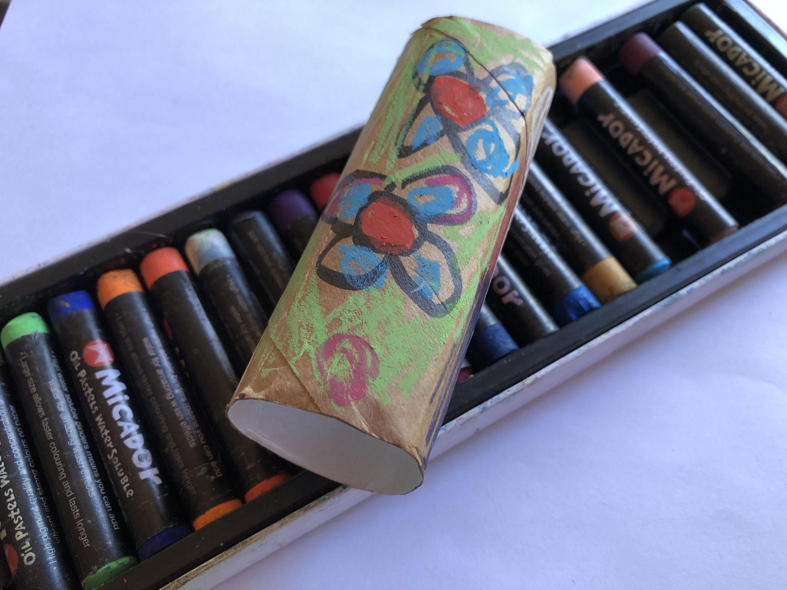 Oil pastels are perfect for making bright marks on dull brown cardboard.