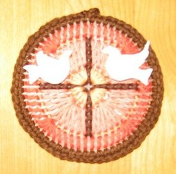 Plastic canvas circle with stitched cross and fimo doves