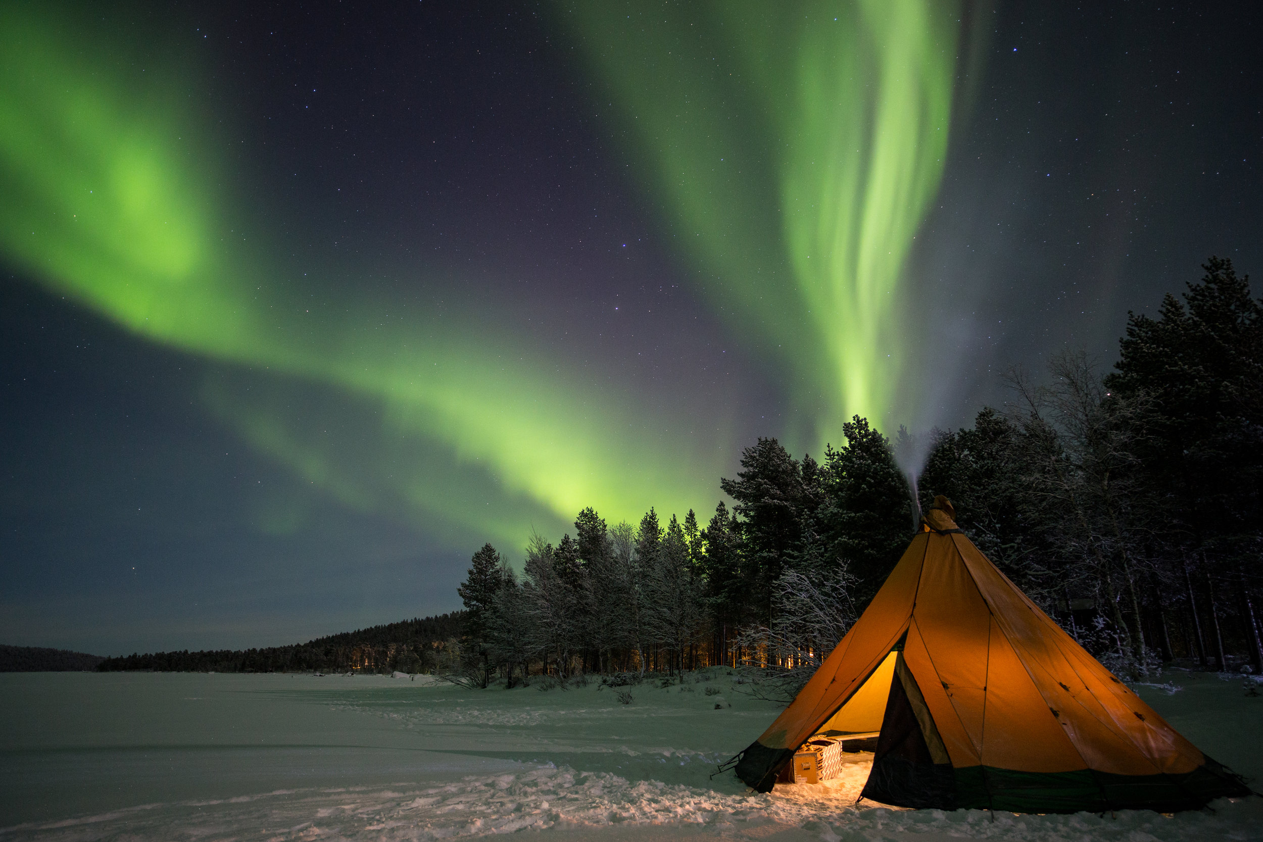Aurora Borealis over a fire tipi on the shore of Ukonjarvi.