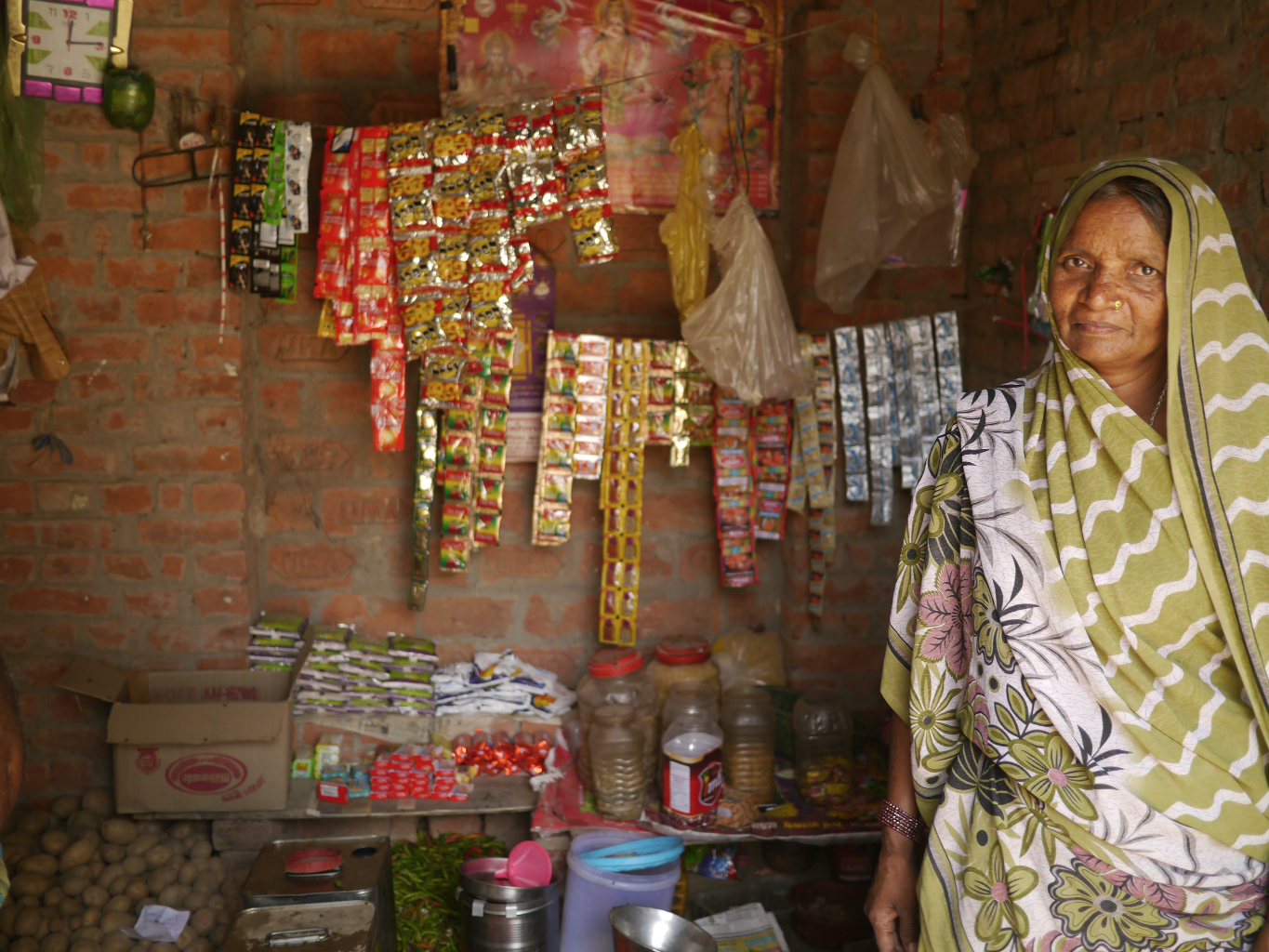 A woman shows off her wares. This single room serves as living and workspace for her and her family and now is also used to secure the tablets.