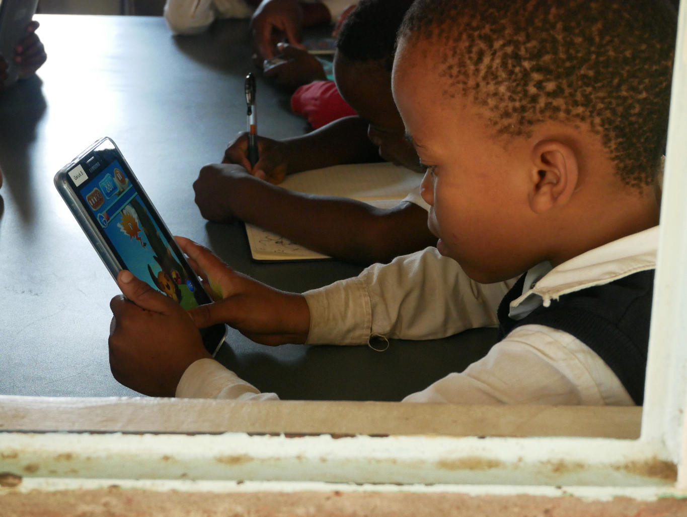 Early testing of Feed the Monster. This girl is using the isiZulu version of the Feed the Monster app that teaches early literacy skills. This app is now available in all 11 official South African languages.