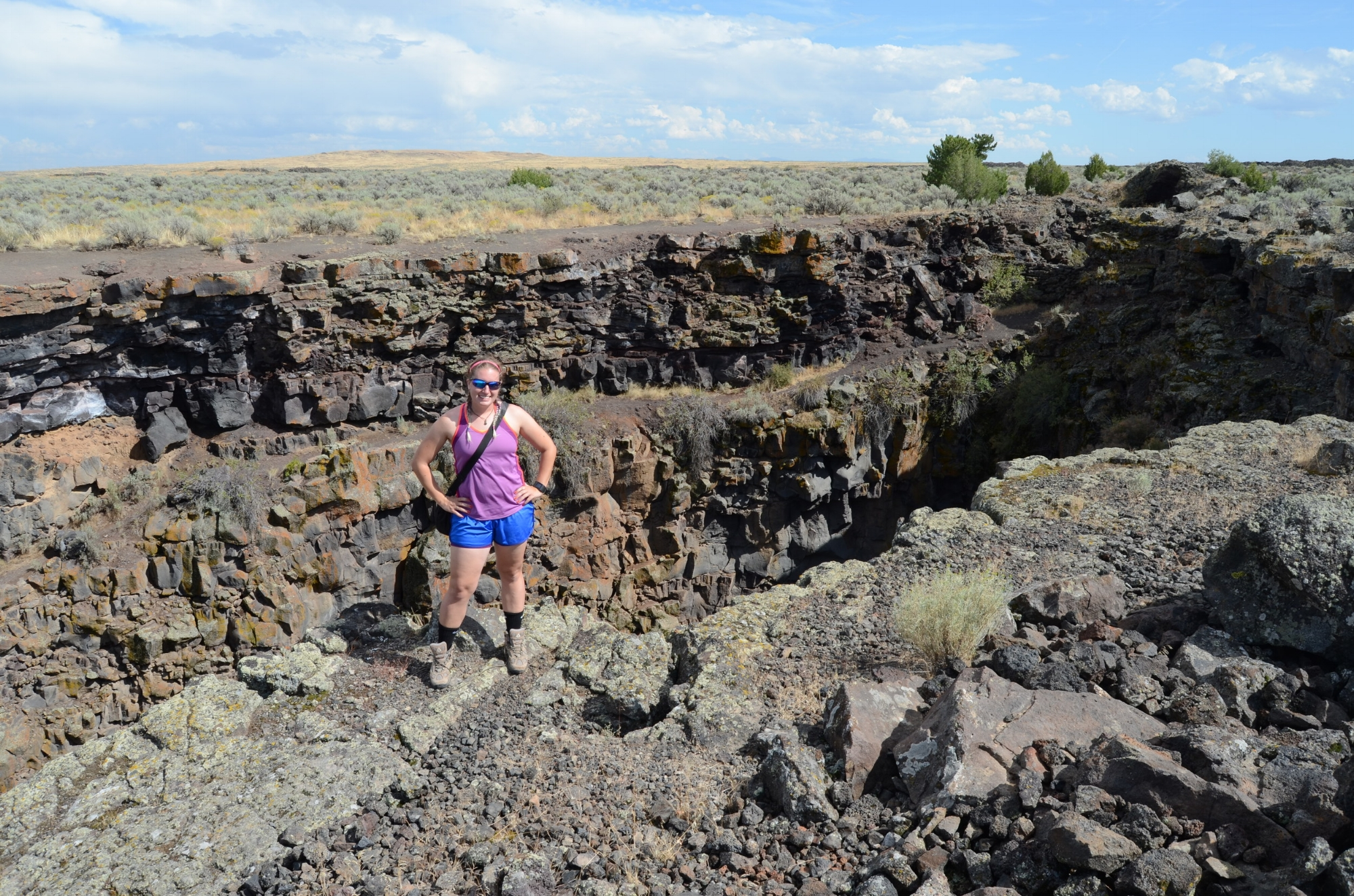 Nicki Button conducting fieldwork at Kings Bowl, an explosive volcanic vent that once ejected many large blocks in Craters of the Moon National Monument and Preserve. Button looked at the block distribution around the vent as an analog site to volcanic vents on early Mars. Photo compliments of Nicki Button.