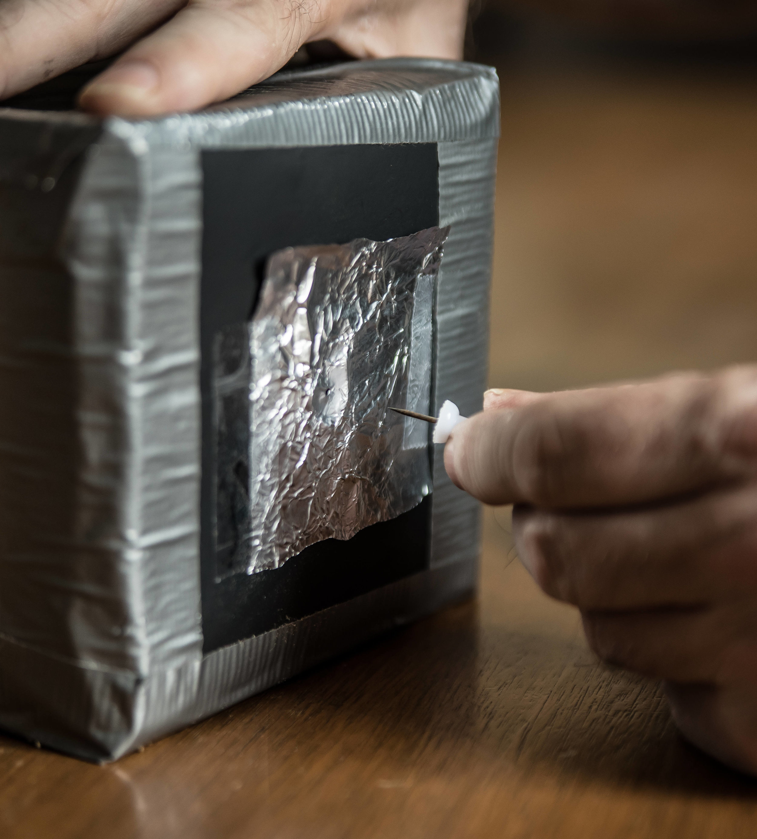 Tape foil over the hole you just made. Then, make a new small hole with a safety pin.