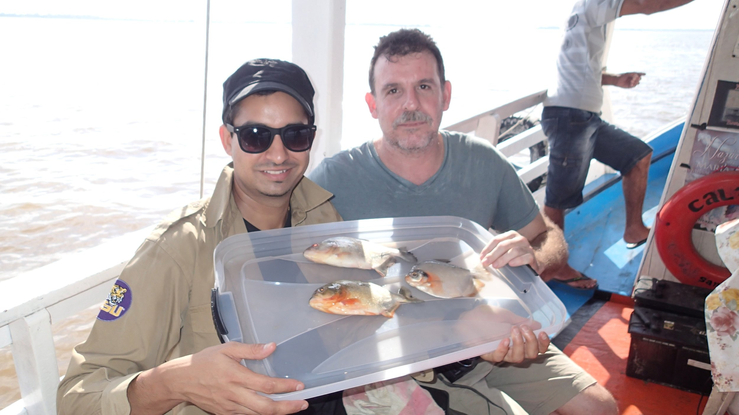 A photo of Prosanta Chakrabarty and collaborator James Albert with fish they collected during a field expedition on the Brazilian Amazon.