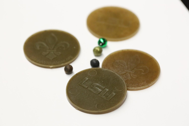LSU biologist  Naohiro Kato  has created biodegradable Mardi Gras beads. Photo by Paige Jarreau.