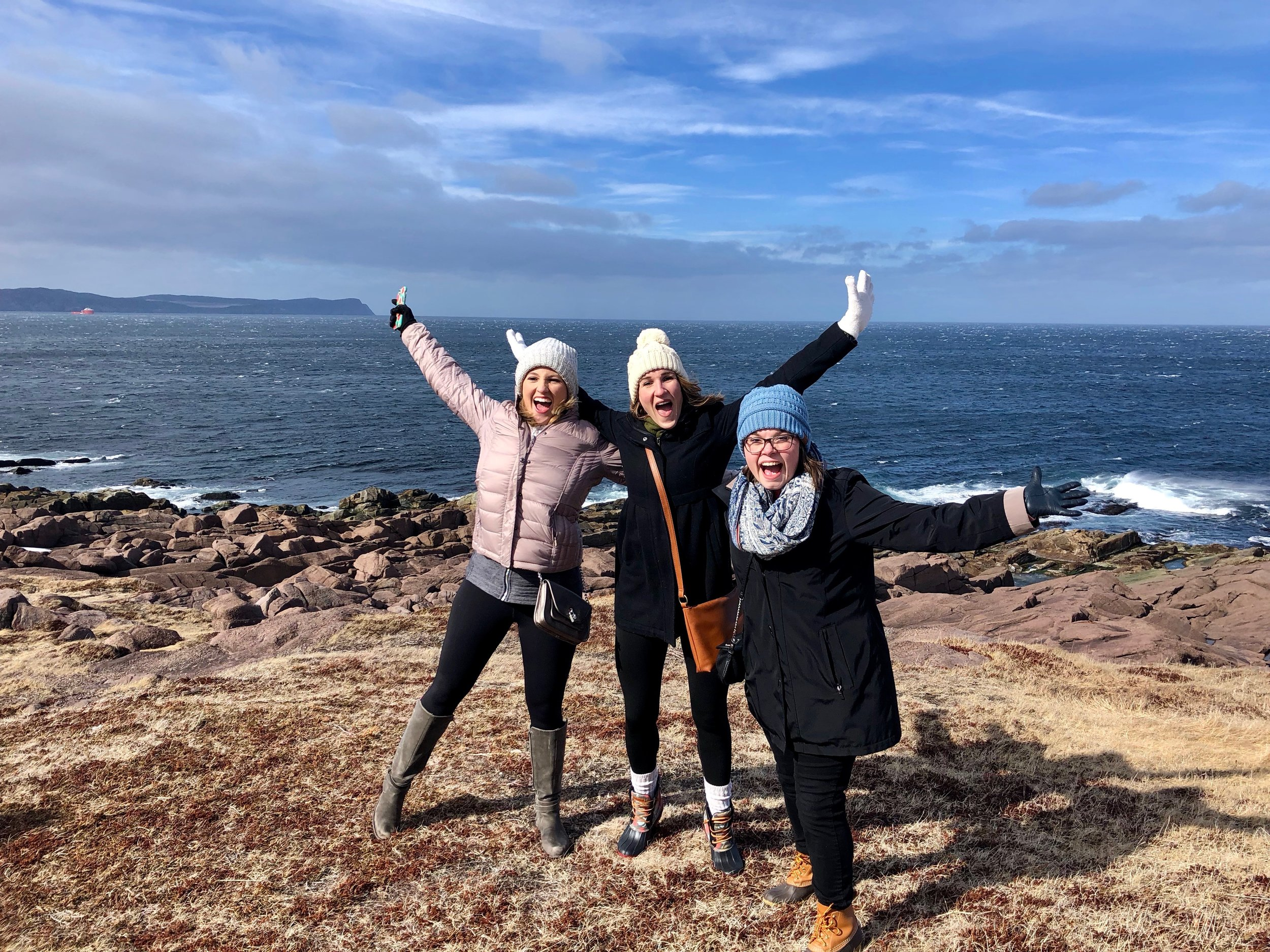 "Anna (left), Alicia (center), Megan (right) being ""taken"" by the wind at Cape Spear. Credit: Anna Lucchesi"