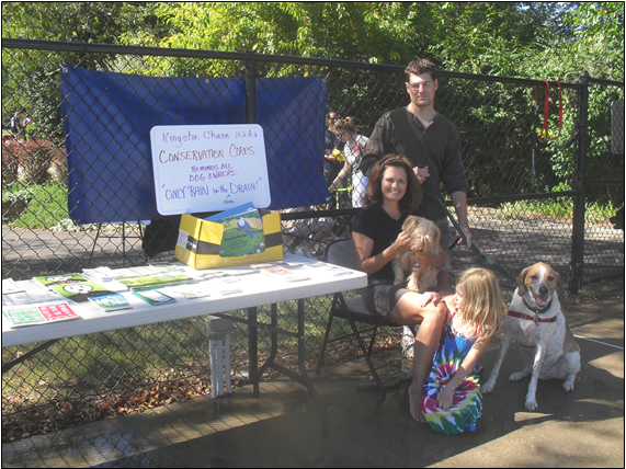 Jane Hampson, seated, sponsored a Conservation Corps booth at the 2010 Dog Day at the Pool.