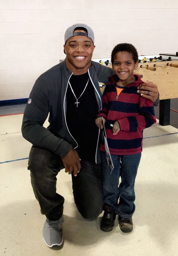 CJ Ham posing with a child from the Boys & Girls Club after signing an autograph.