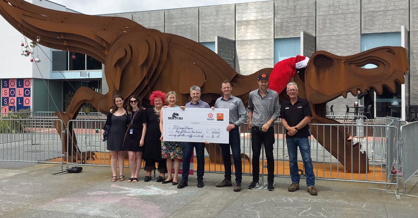 Representatives from Te Omanga Hospice, Macaulay Metals and Real Steel holding the cheque in front of Colin the T-Rex
