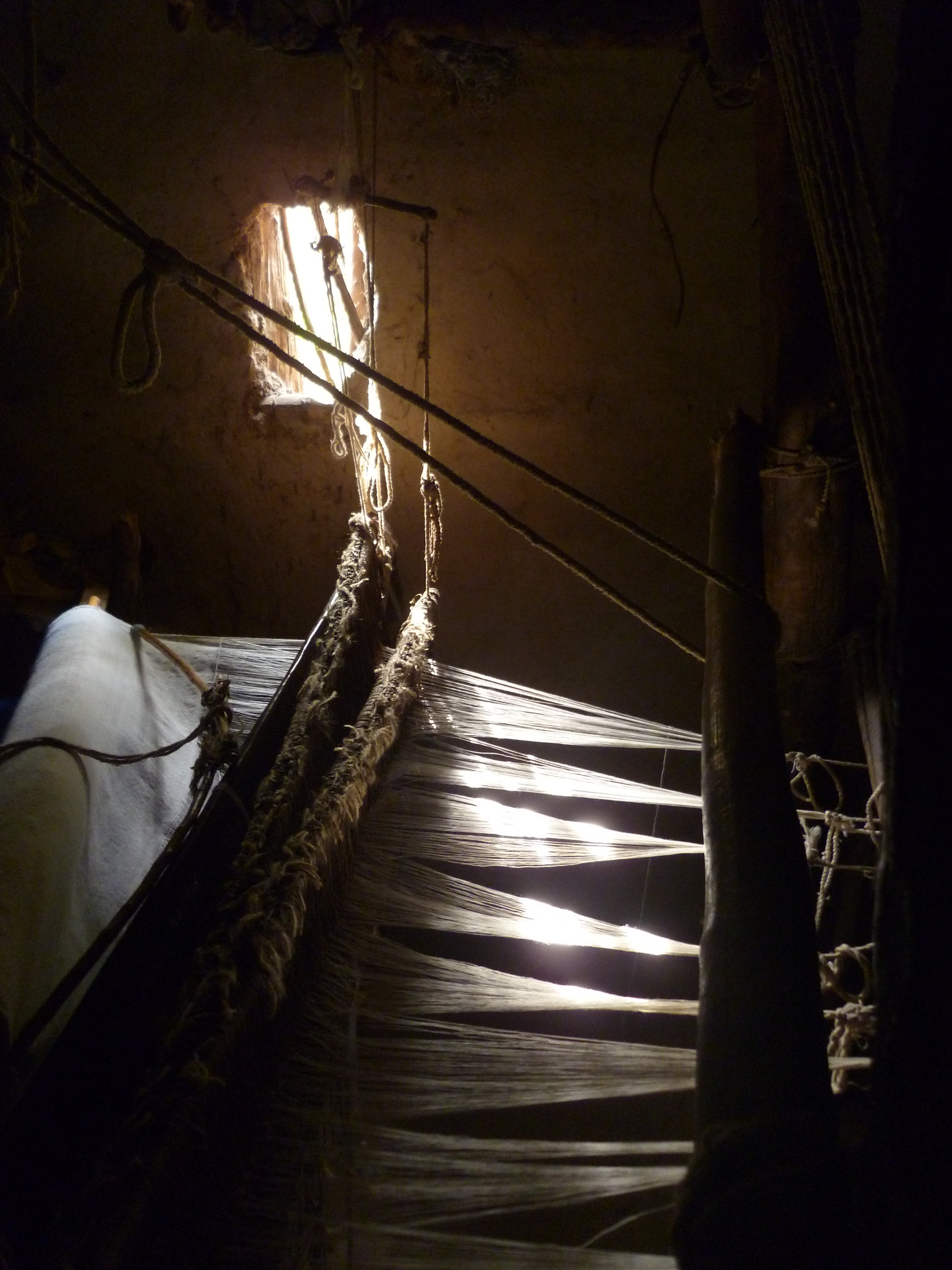 Sunlight pouring through the workshop windows illuminating the intricate Awra Amba weaving...