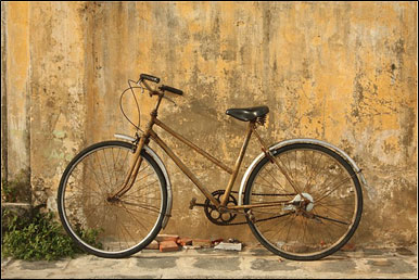 bicycle leaning against a gold colored wall