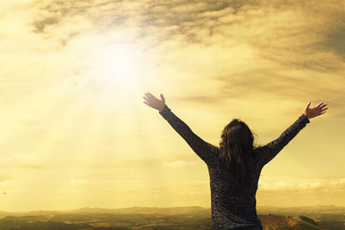 woman looking to the sky with hands raised
