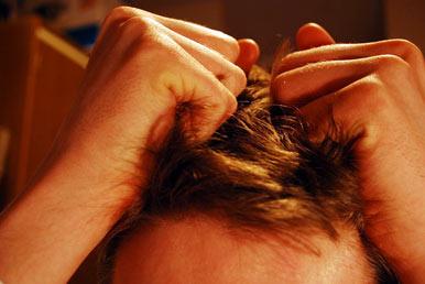 man pulling at his hair